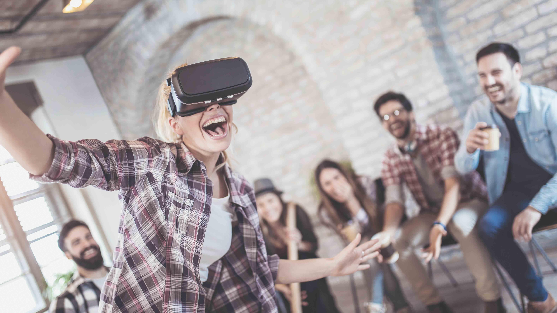Femme avec un casque VR jouant devant ses amis