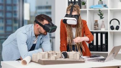 Architectes portant casques VR autour d'une maquette de bâtiment