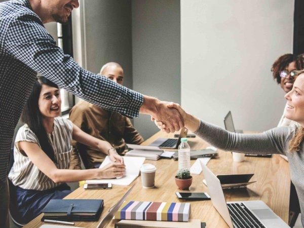 deux personnes qui se serrent la main dans une salle de réunion
